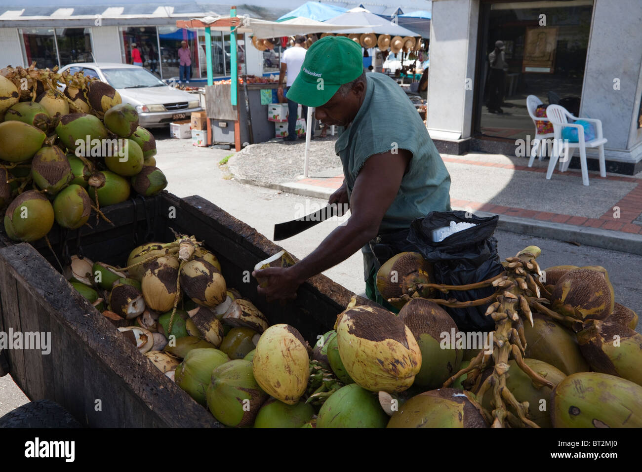 man cutting up coconuts to sell the milk from a barrow. Black Bedroom Furniture Sets. Home Design Ideas