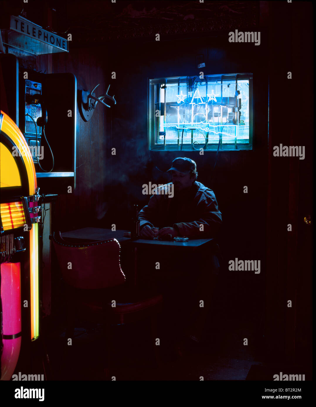 man drinking, interior of bar, lit daylight and neon, Stock Foto