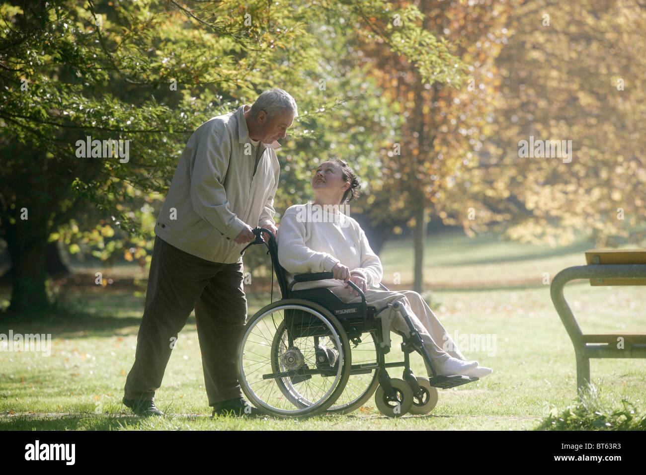 Old Man Pushing Woman On Wheelchair Stock Photo: 32096823