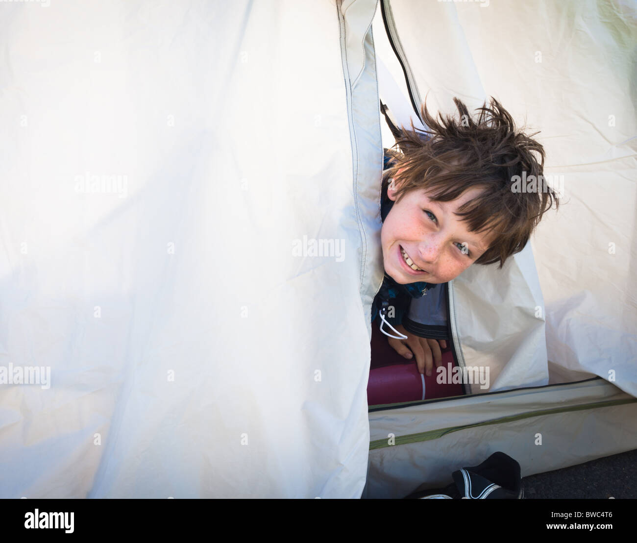 Boy looking out of tent Stock Foto