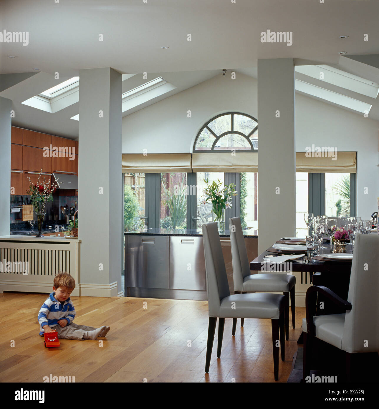 Small Boy Sitting On Wooden Floor Of Modern Kitchen Dining