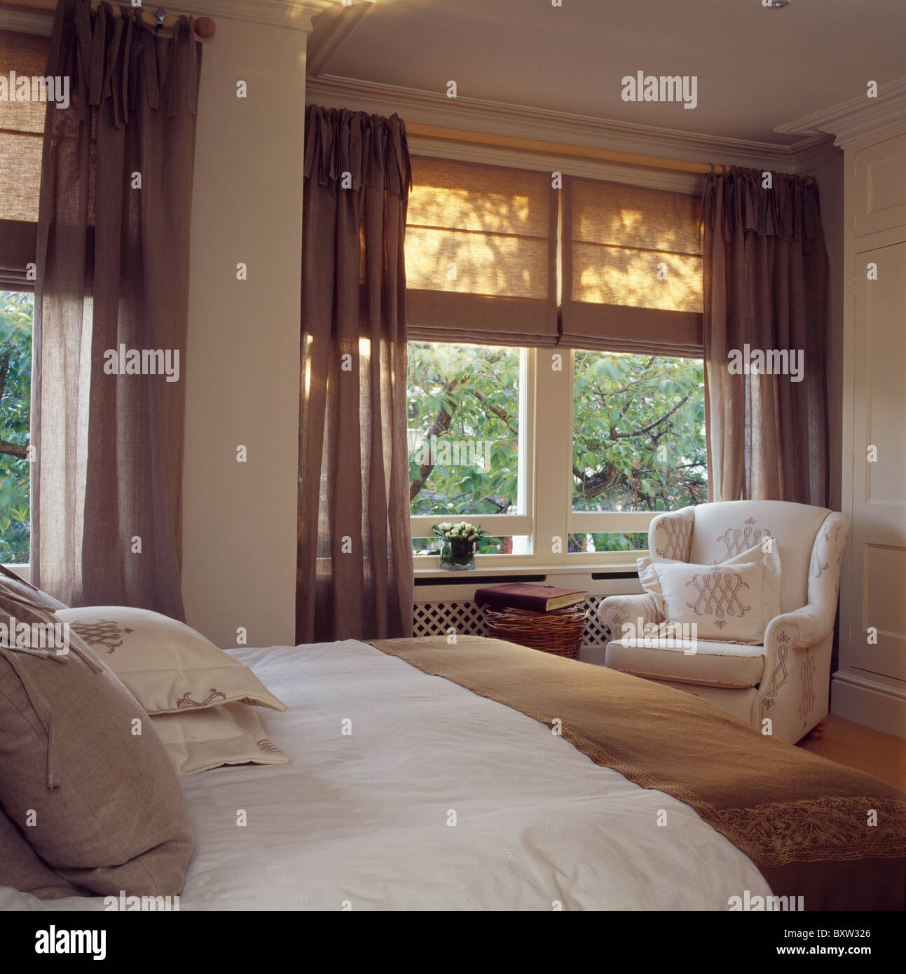 cream linen blinds and brown voile curtains on windows in cream stock