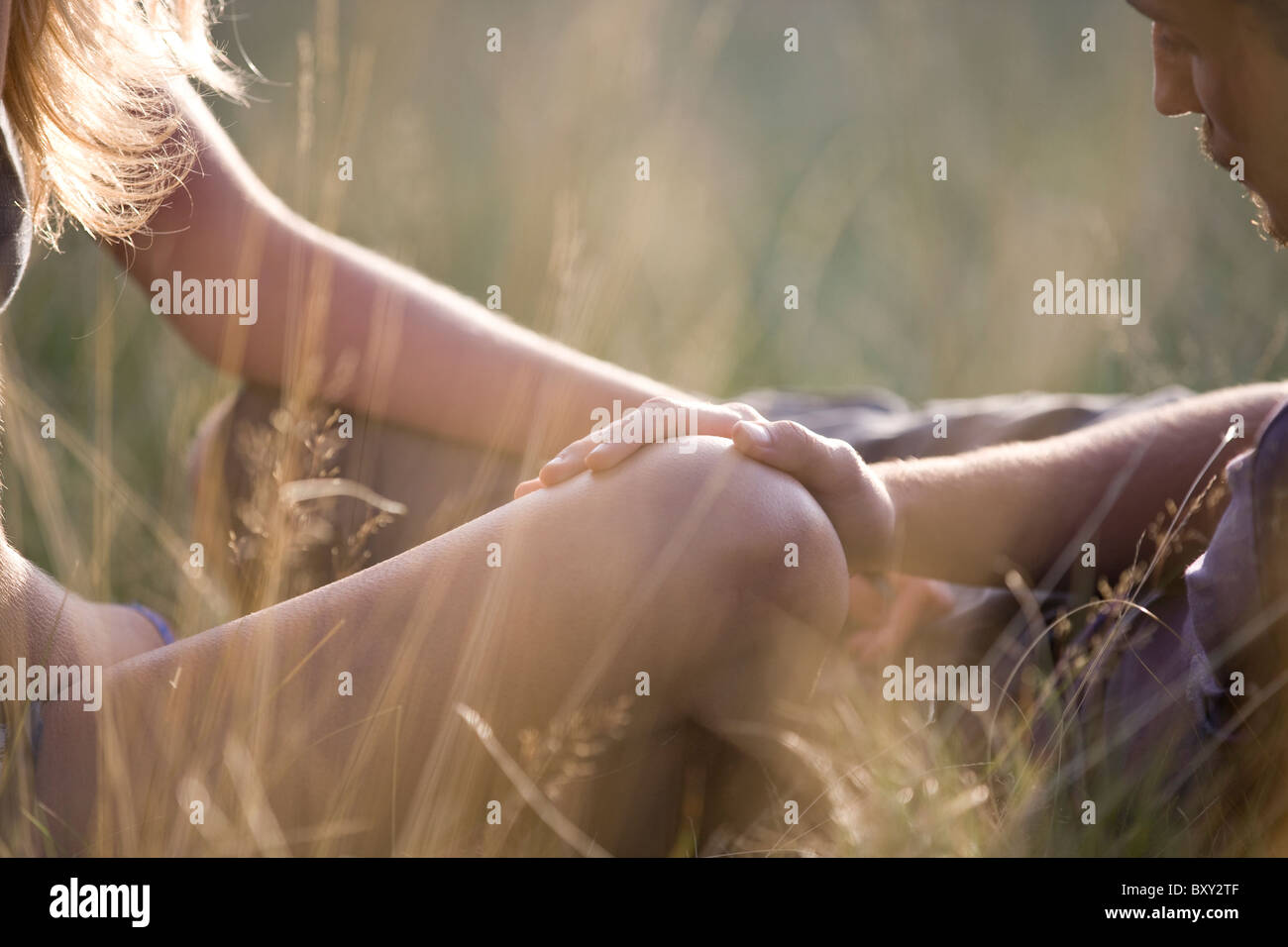 Detail of a young couple outdoors, mans hand on the womans knee Stock Foto