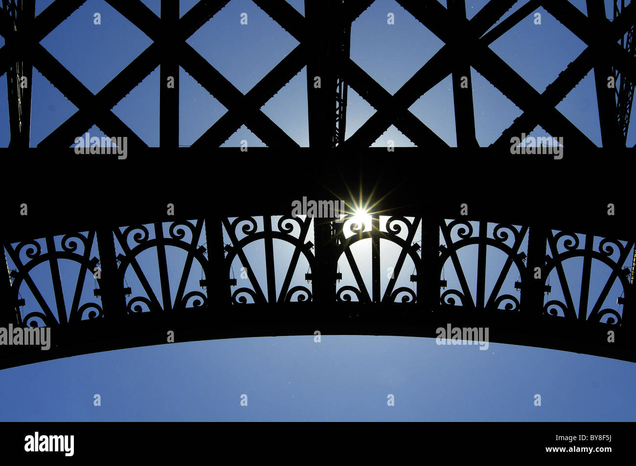 the-sun-shining-through-the-arch-of-the-eiffel-tower-in-paris-BY8F5J.jpg