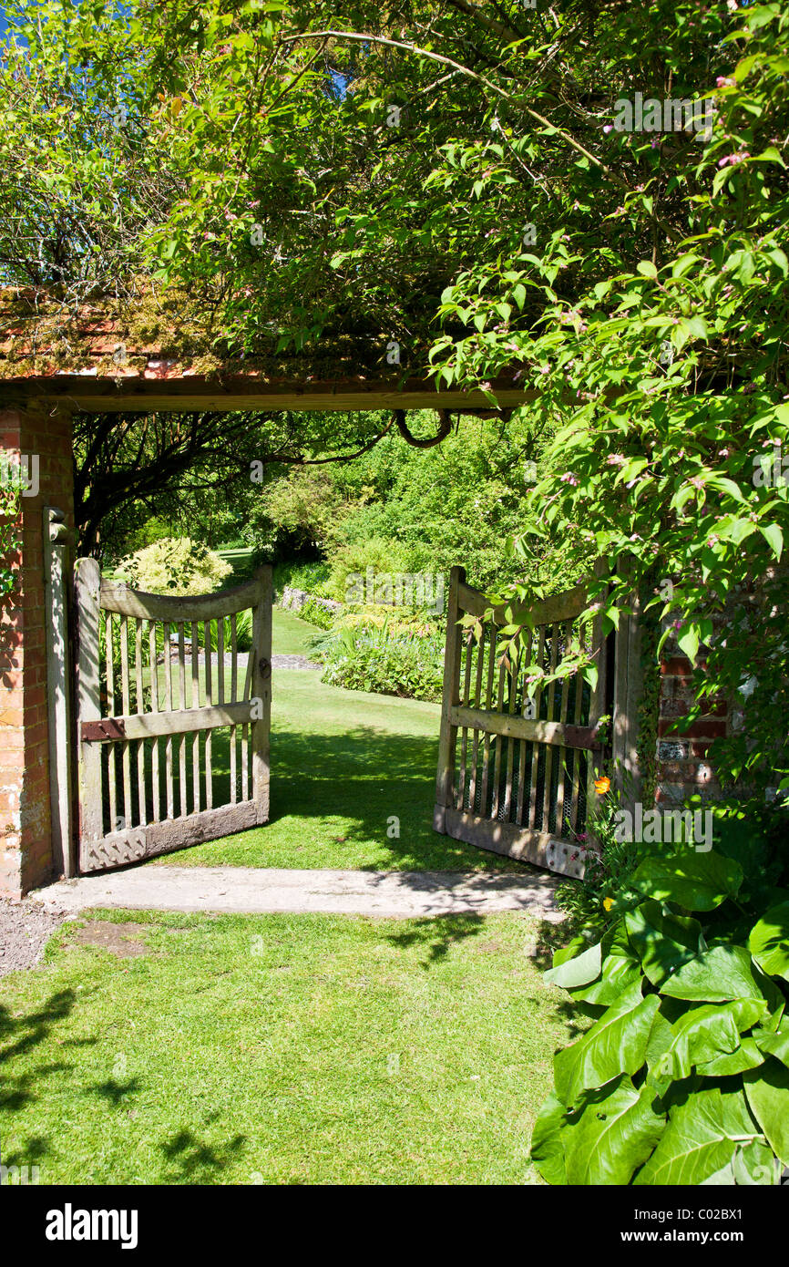 An open wooden garden gate in english country