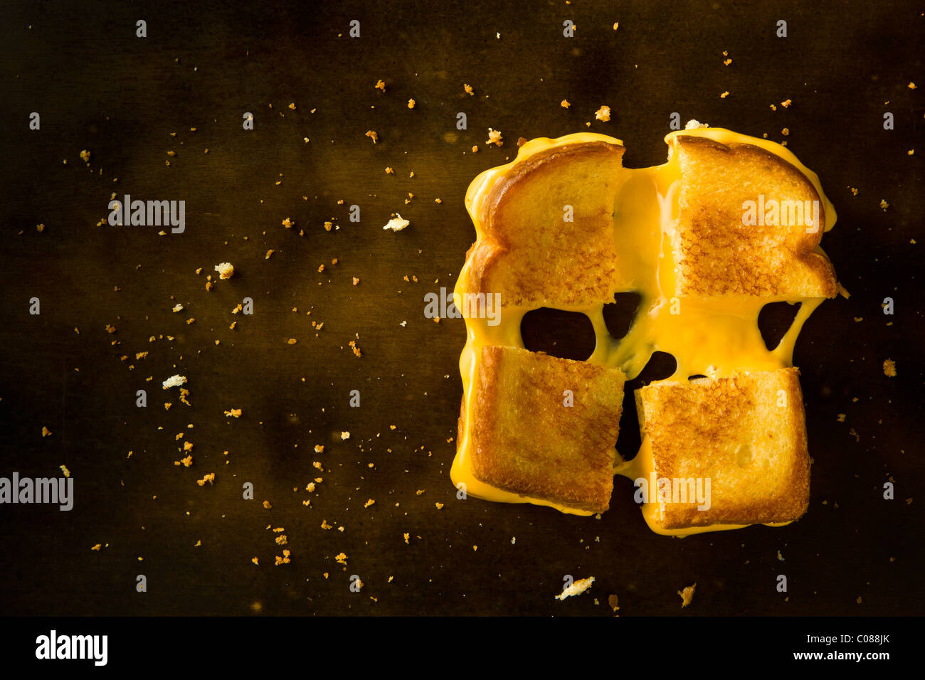 A Grilled Cheese Sandwich cut in four squares pulling the cheese on a wood table Stock Photo