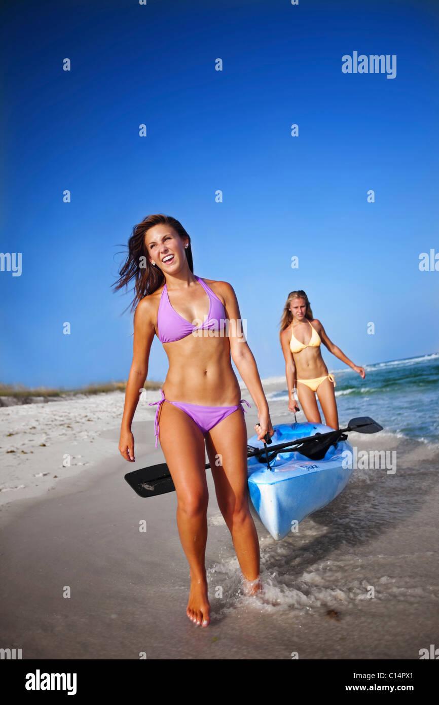 Two Girls Walk With A Sea Kayak Along Pensacola Beach Florida Stock Photo Royalty Free Image