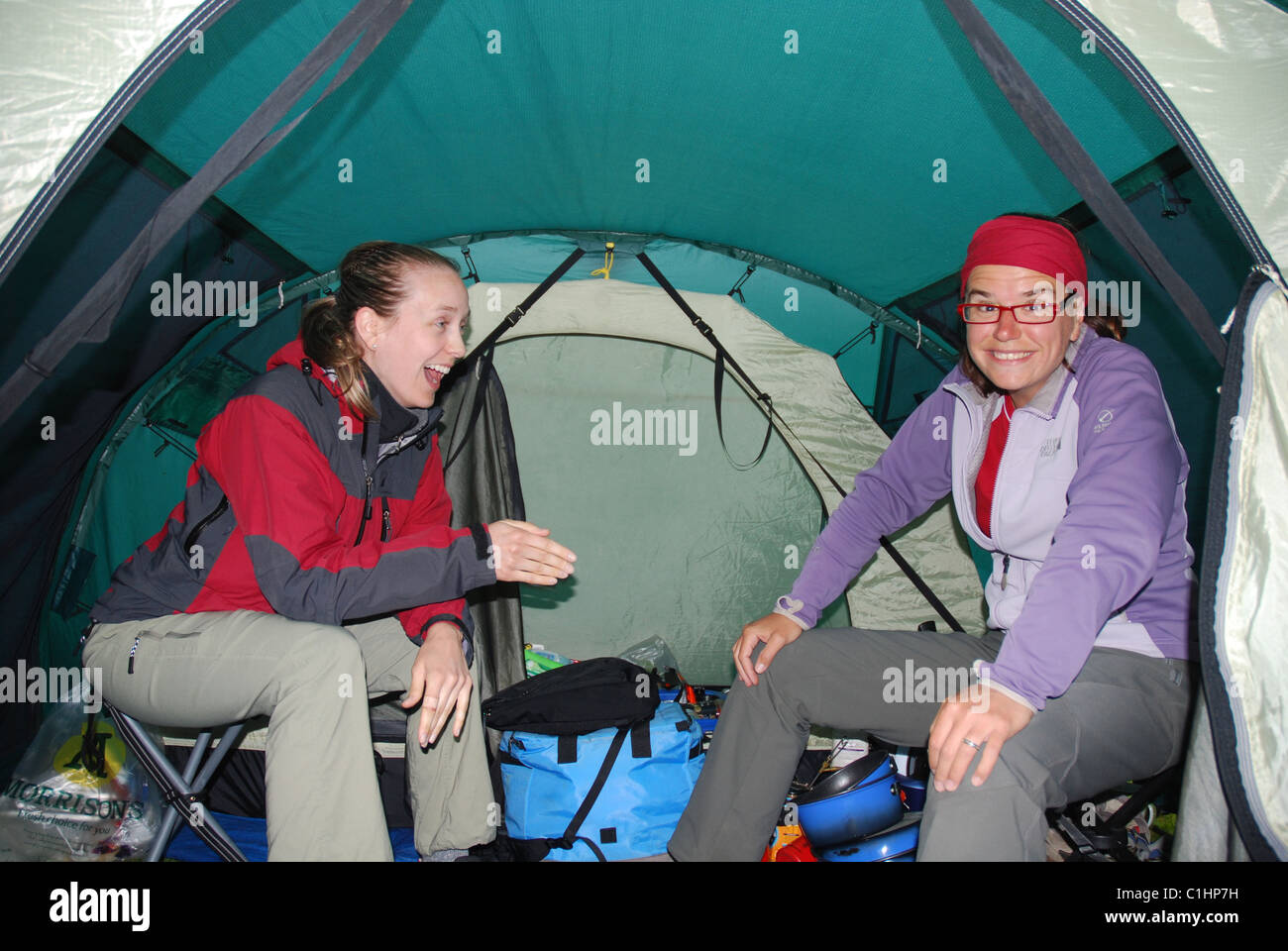 two-women-laughing-in-a-tent-C1HP7H.jpg