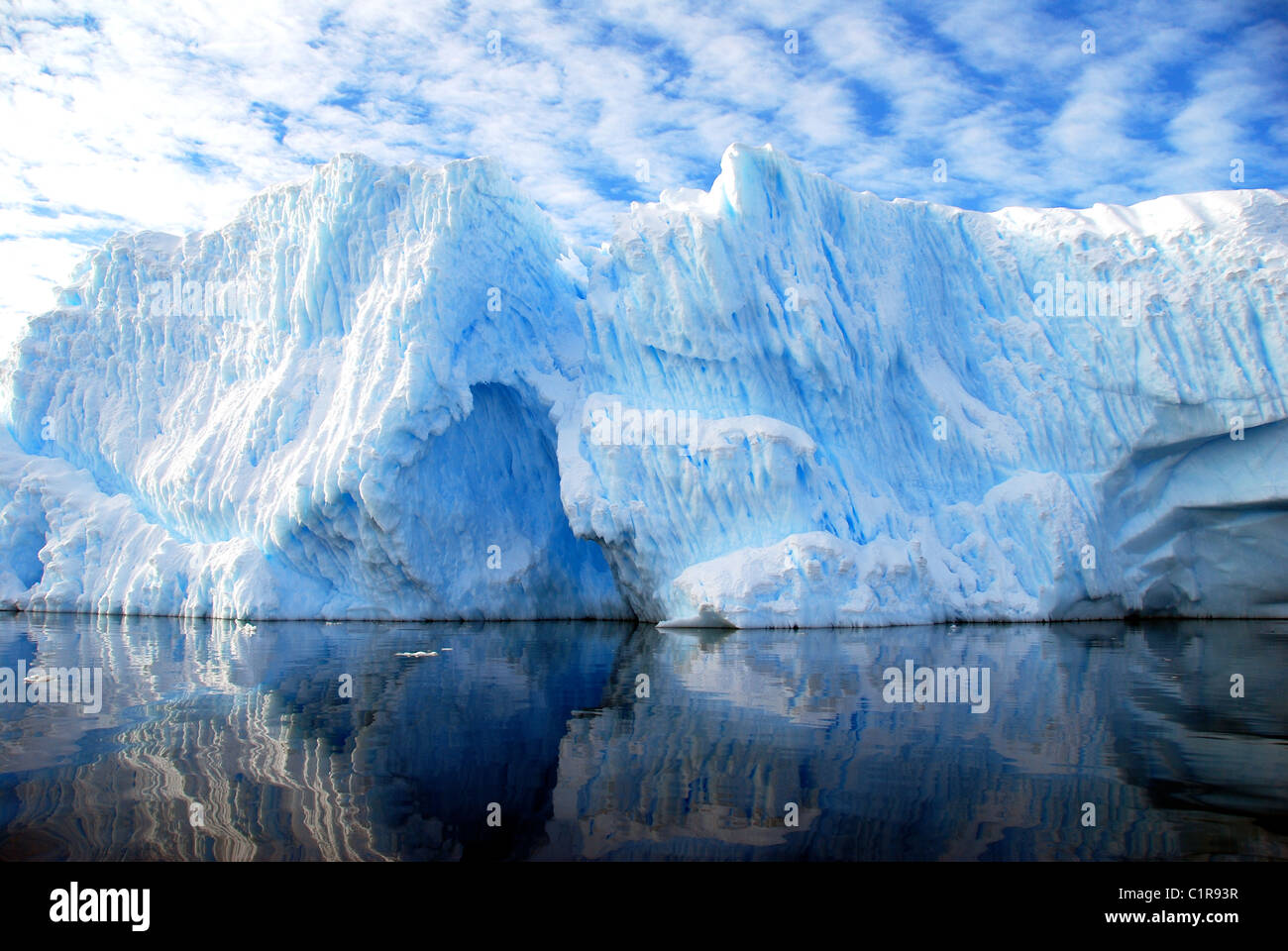 striated iceberg with blue sky and dramatic clouds Stock Foto