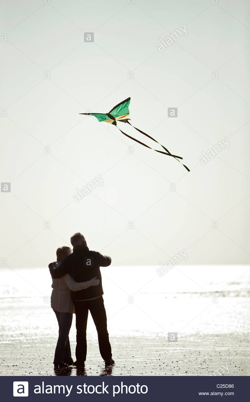 A senior couple flying a kite on the beach, rear view Stock Foto
