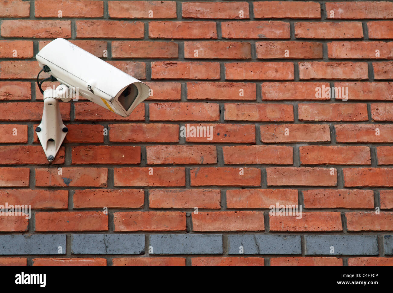 white-cctv-camera-mounted-on-a-red-brick