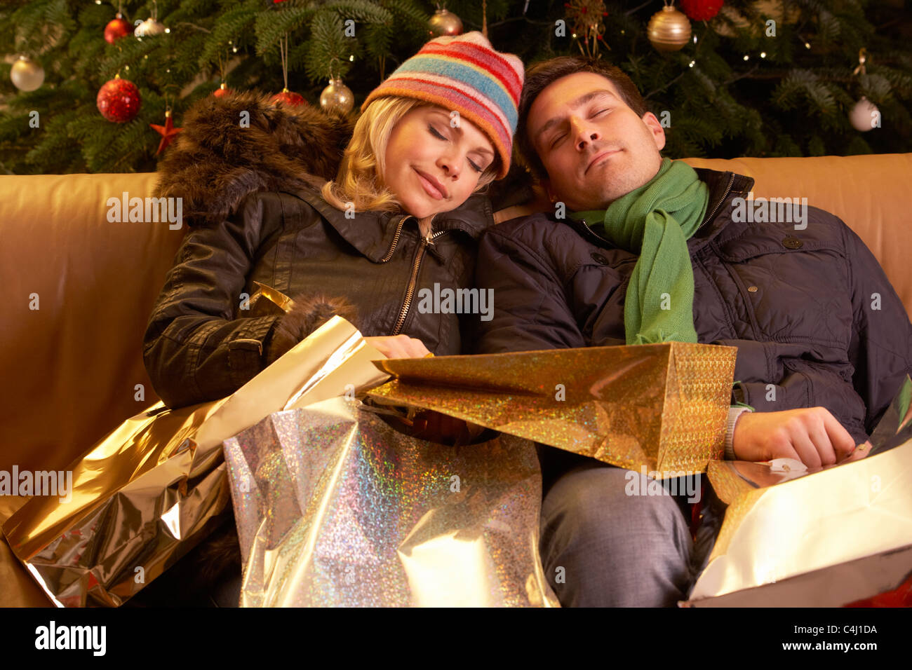 Tired Couple Returning After Christmas Shopping Trip Stock Photo