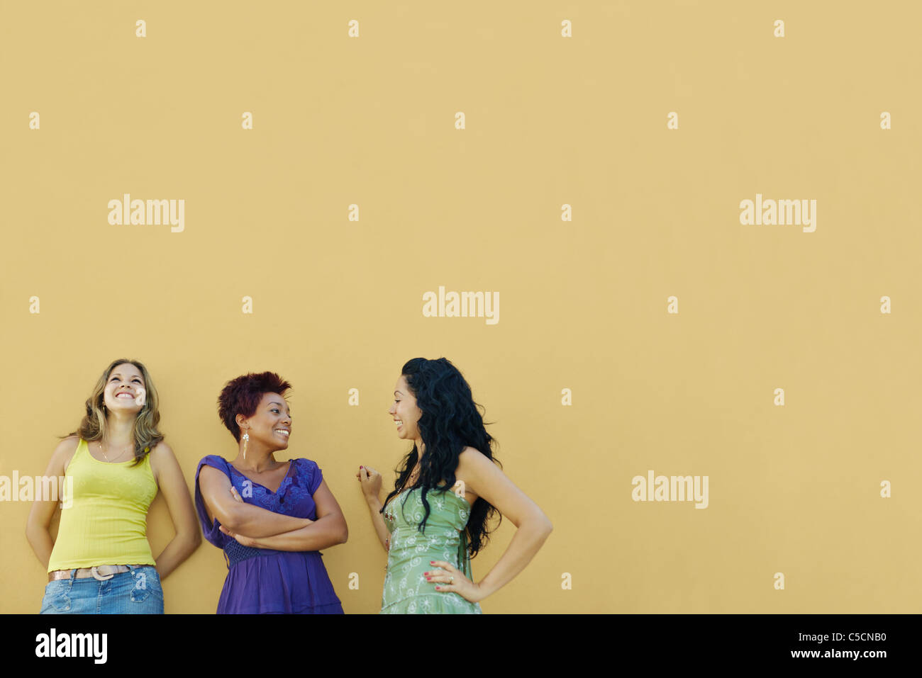 group of three female hispanic friends leaning on yellow wall and laughing. Horizontal shape, waist up, copy space Stock Foto