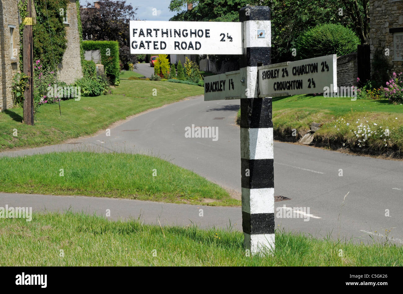 Old Black and White Road Sign in Hinton in the Hedges showing directions to Farthinghoe via a Gated Road Stock Photo