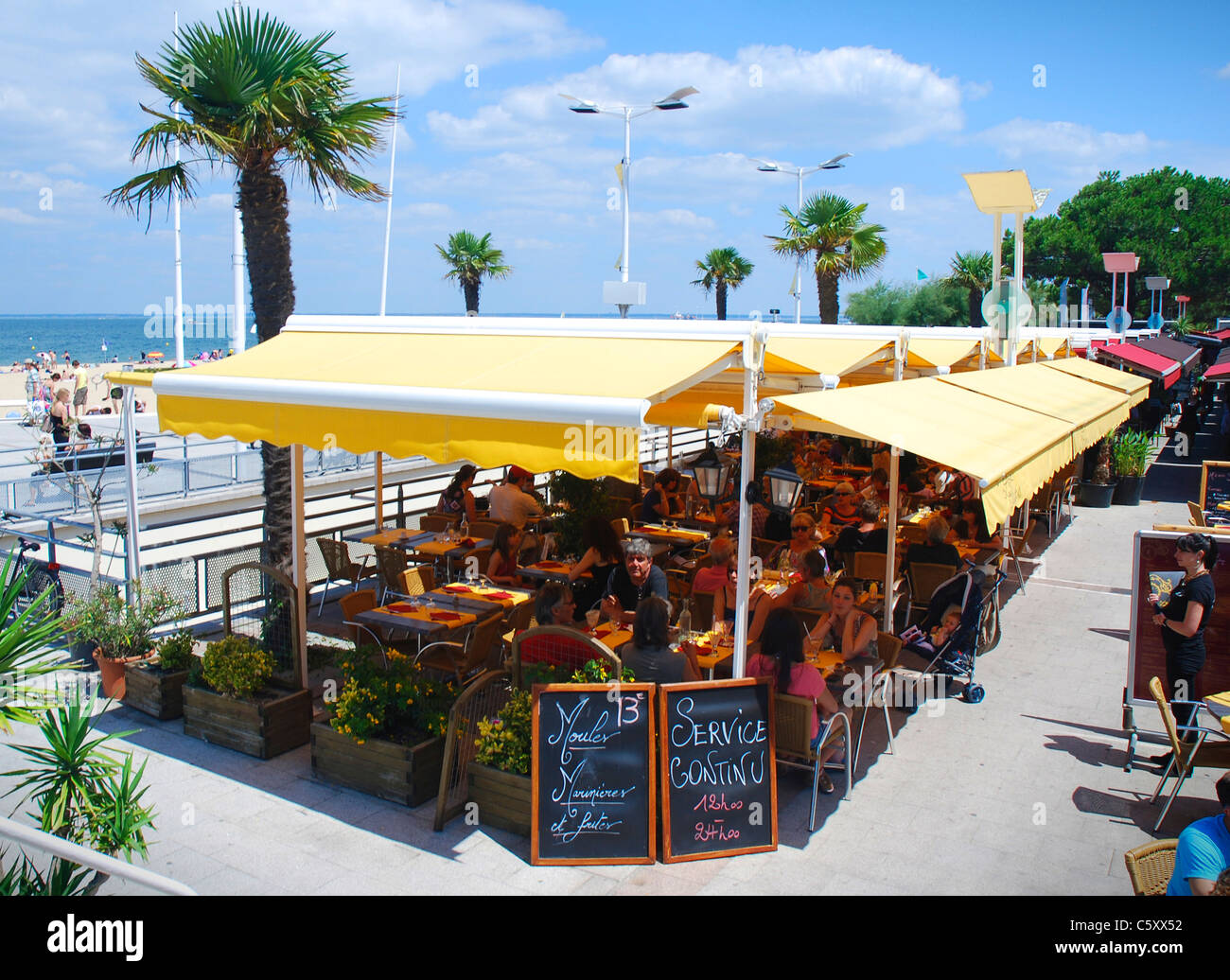 people relaxing at the le thiers arcachon restaurant by the beach in stock photo royalty free. Black Bedroom Furniture Sets. Home Design Ideas