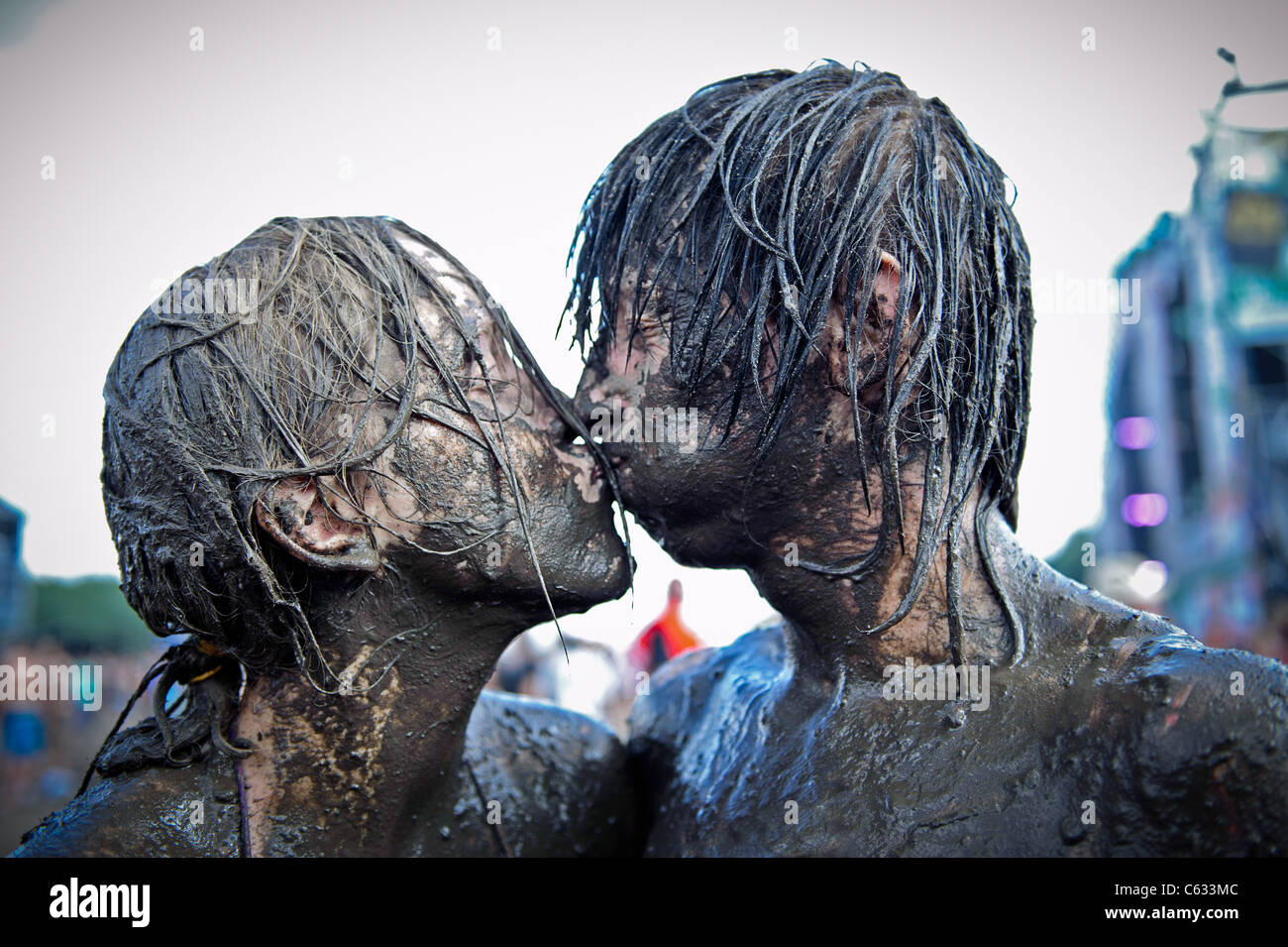 young couple kissing covered in mud at the Przystanek Woodstock - Europe's largest open air festival in Kostrzyn, Stock Foto