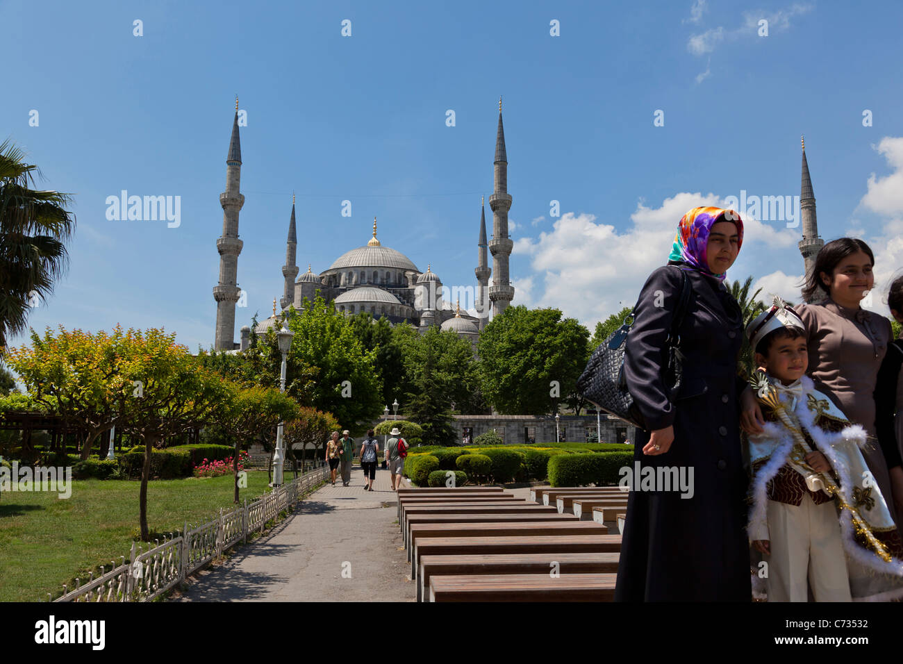 Young Turkish boy in their ceremonial circumcision outfit, posing with his family, outside the The Blue Mosque, Stock Photo