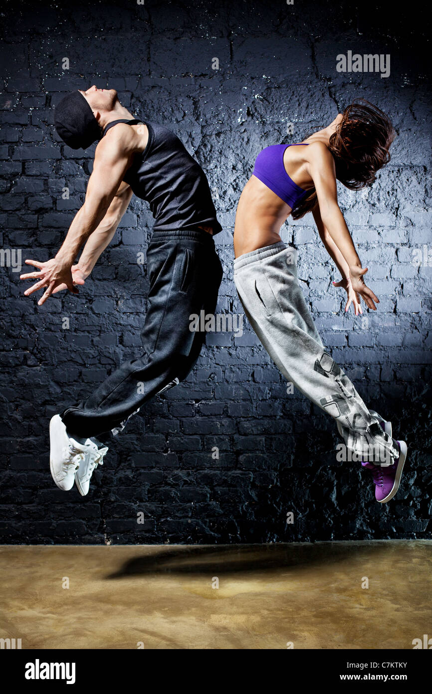 Young dancer couple jumping. On wall background. Stock Foto