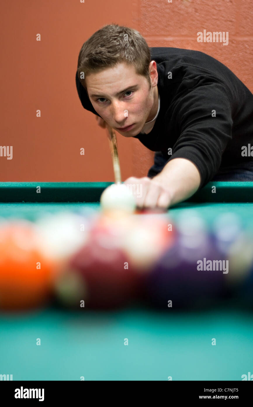 A young man lines up his shot as he breaks the balls for the start of a game of billiards. Shallow depth of field. Stock Foto