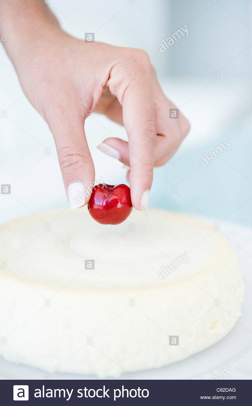Woman putting cherry on the cake Stock Photo, Royalty Free ...