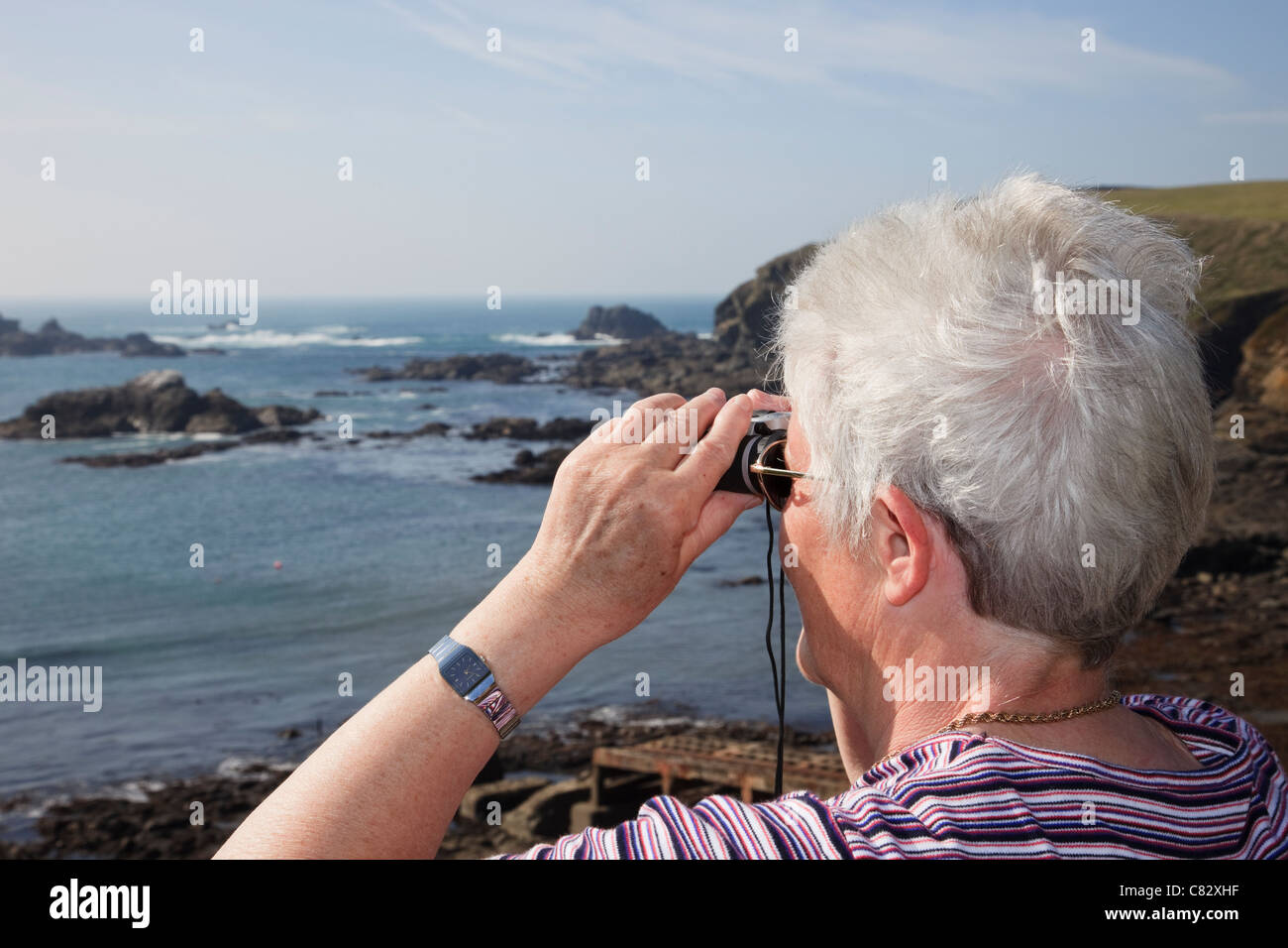 Senior woman looking through binoculars out to sea on coast at most southerly point on mainland Britain. Lizard Stock Foto