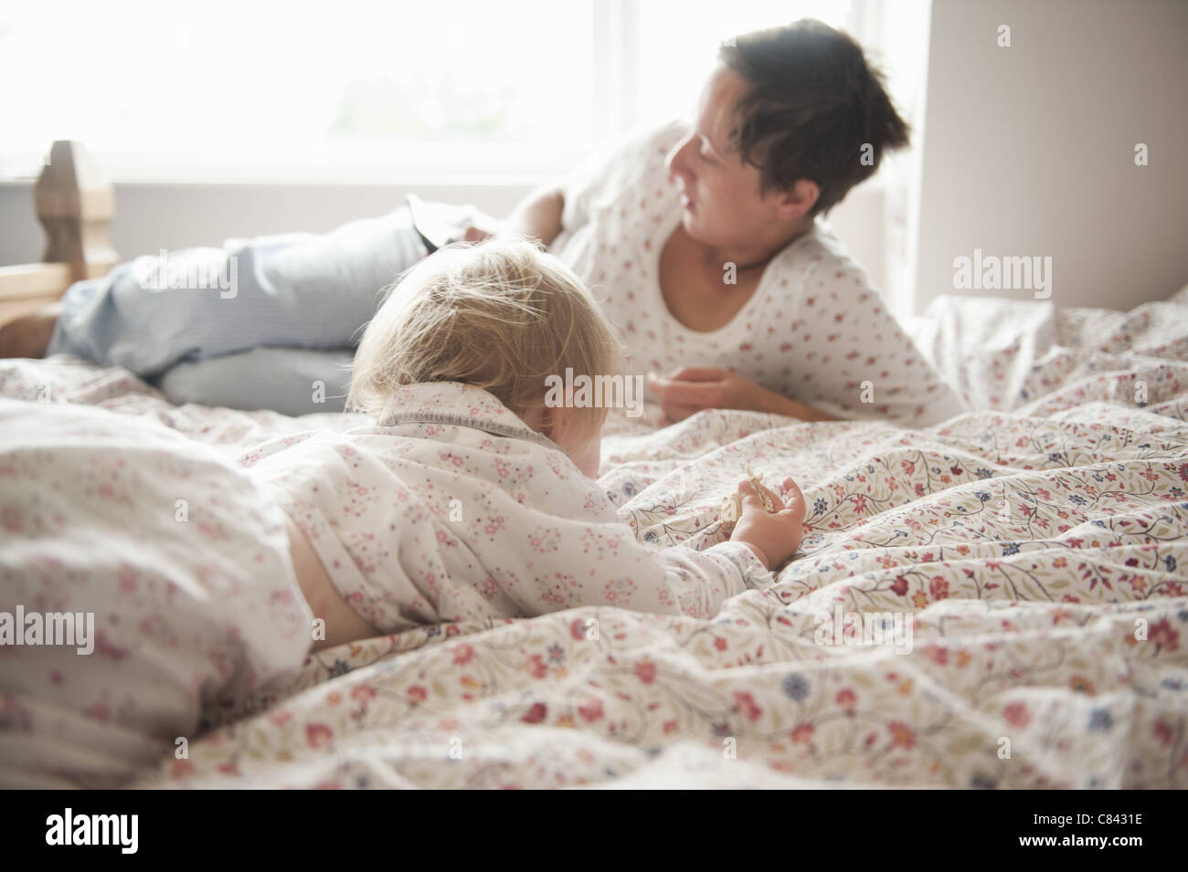 Toddler girl sitting with mother in bed Stock Foto