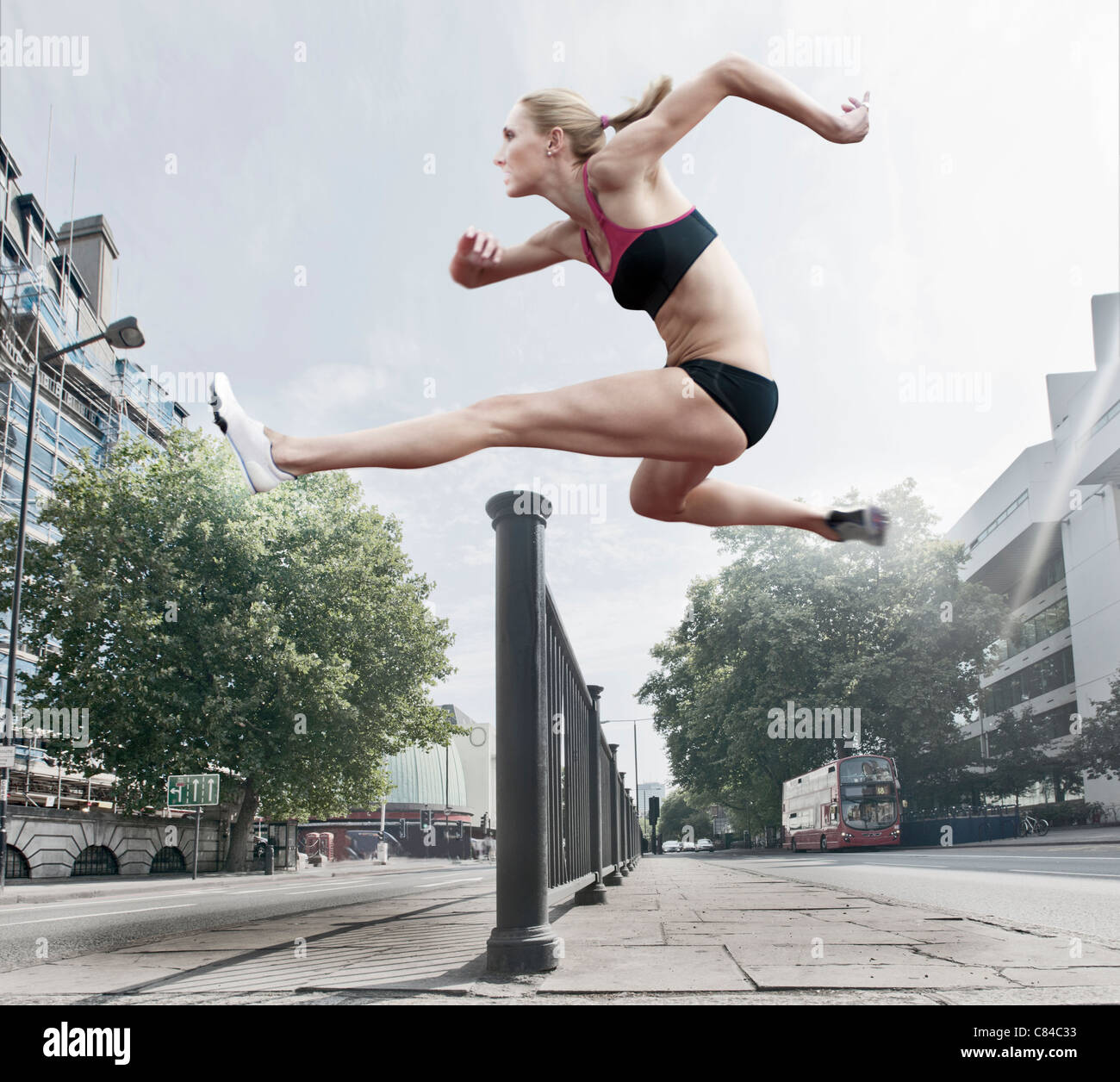 Athlete jumping over banister on street Stock Foto