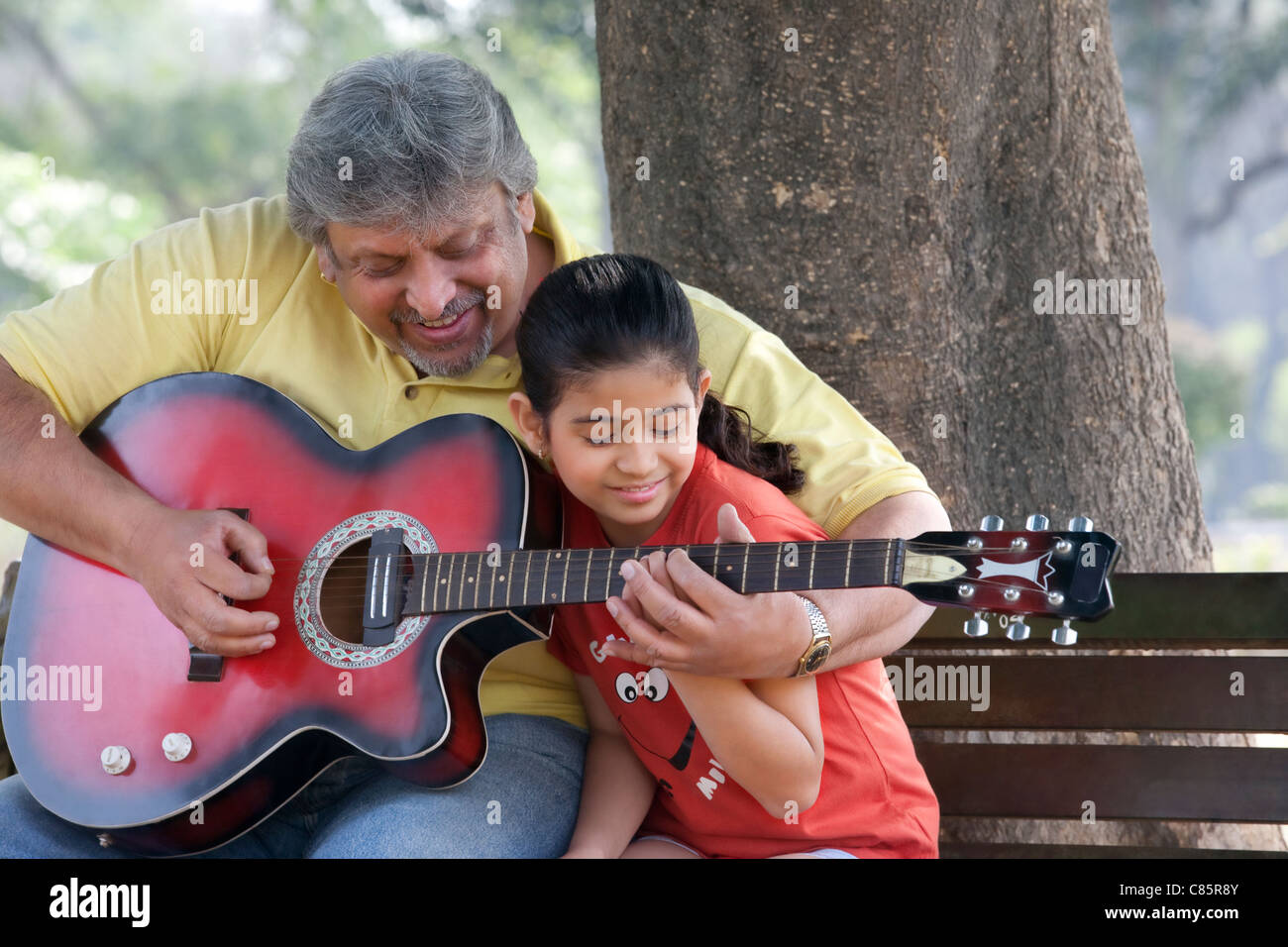 Grandfather teaching his granddaughter to play the guitar Stock Foto