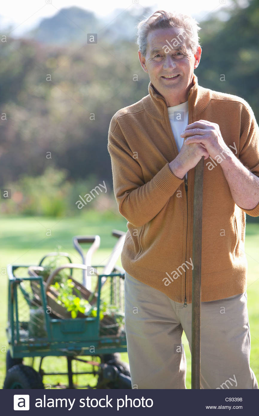 Portrait of smiling senior man with gardening tools Stock Foto