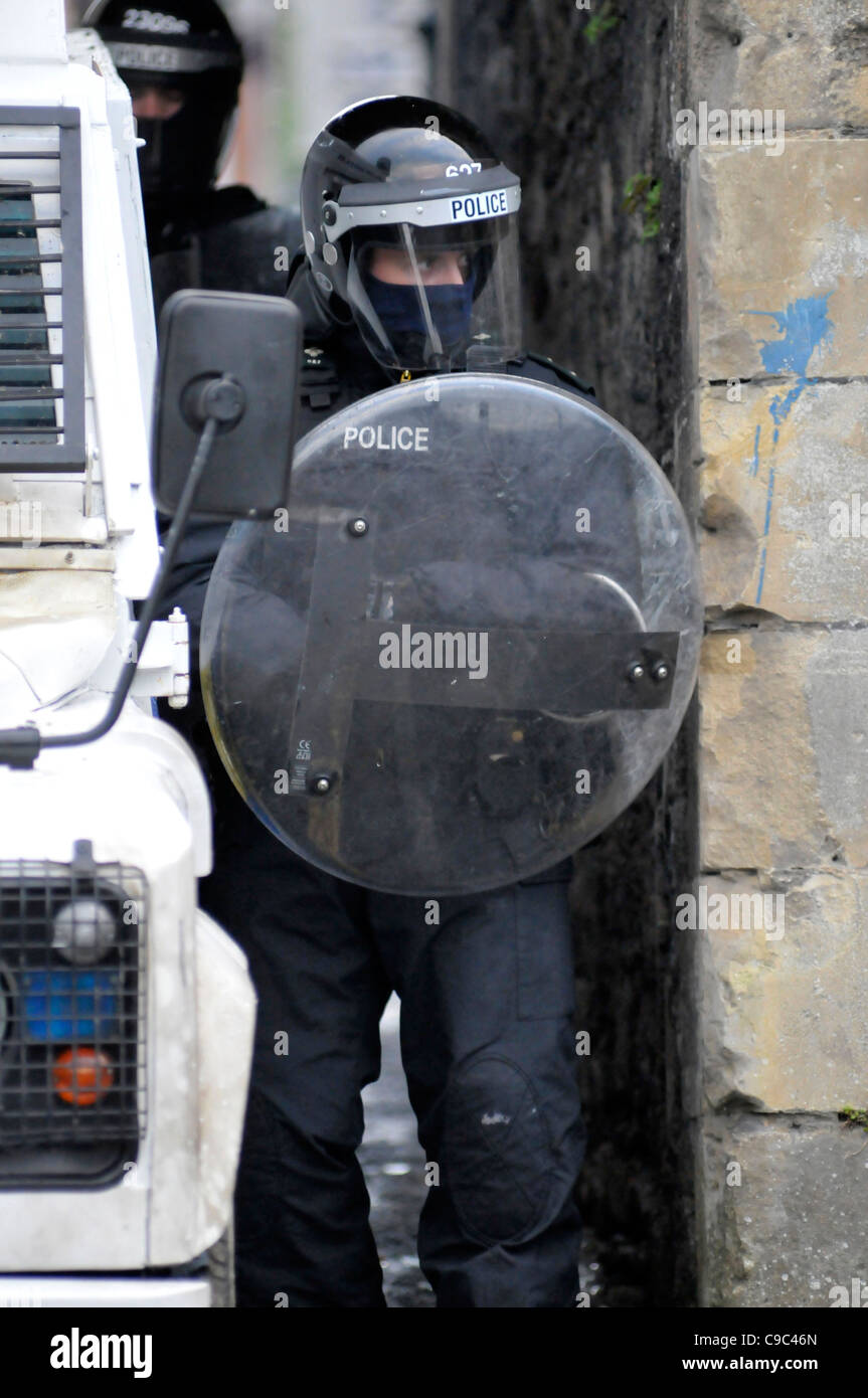 A female PSNI officer with riot shield during disturbances ...