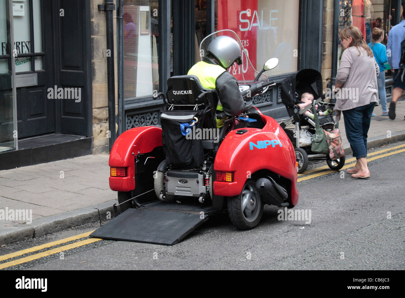 A Man In A Wheelchair Entering A Nippi Three Wheeled Motor