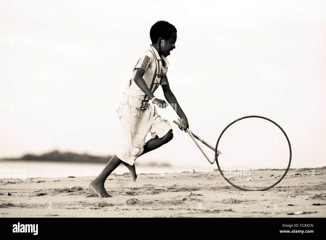 A young malagasy boy 6-10 years running with a stick and a bicycle rim, a traditional toy, at the beach. Nosy Komba, Stock Photo