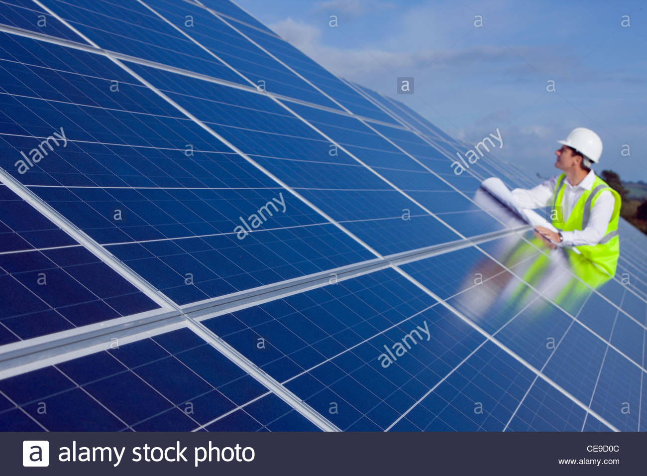 Engineer with blueprint inspecting solar panels stock for Solar panel blueprint