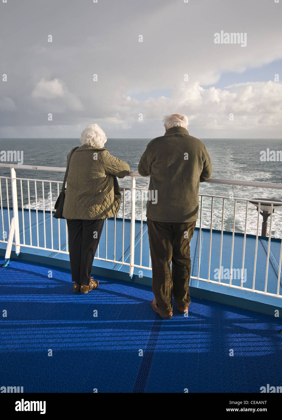Elderly Couple Looking Out To Sea From A Cruise Ship Stock