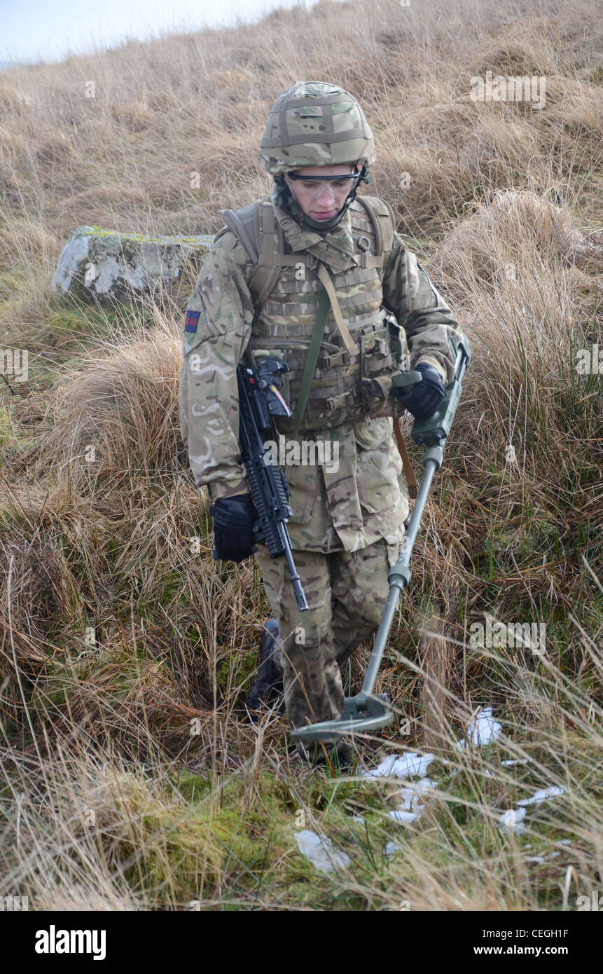 A British army solder 'Vallon man' looking for IED's using a Vallon metal detector, he will lead a patrol, sweeping Stock Photo