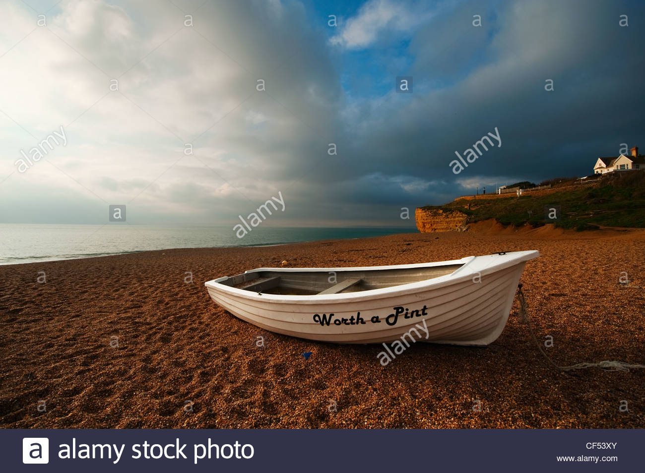 small-boat-on-the-shingle-at-hive-beach-in-dorset-under-dramatic-autumn-CF53XY.jpg