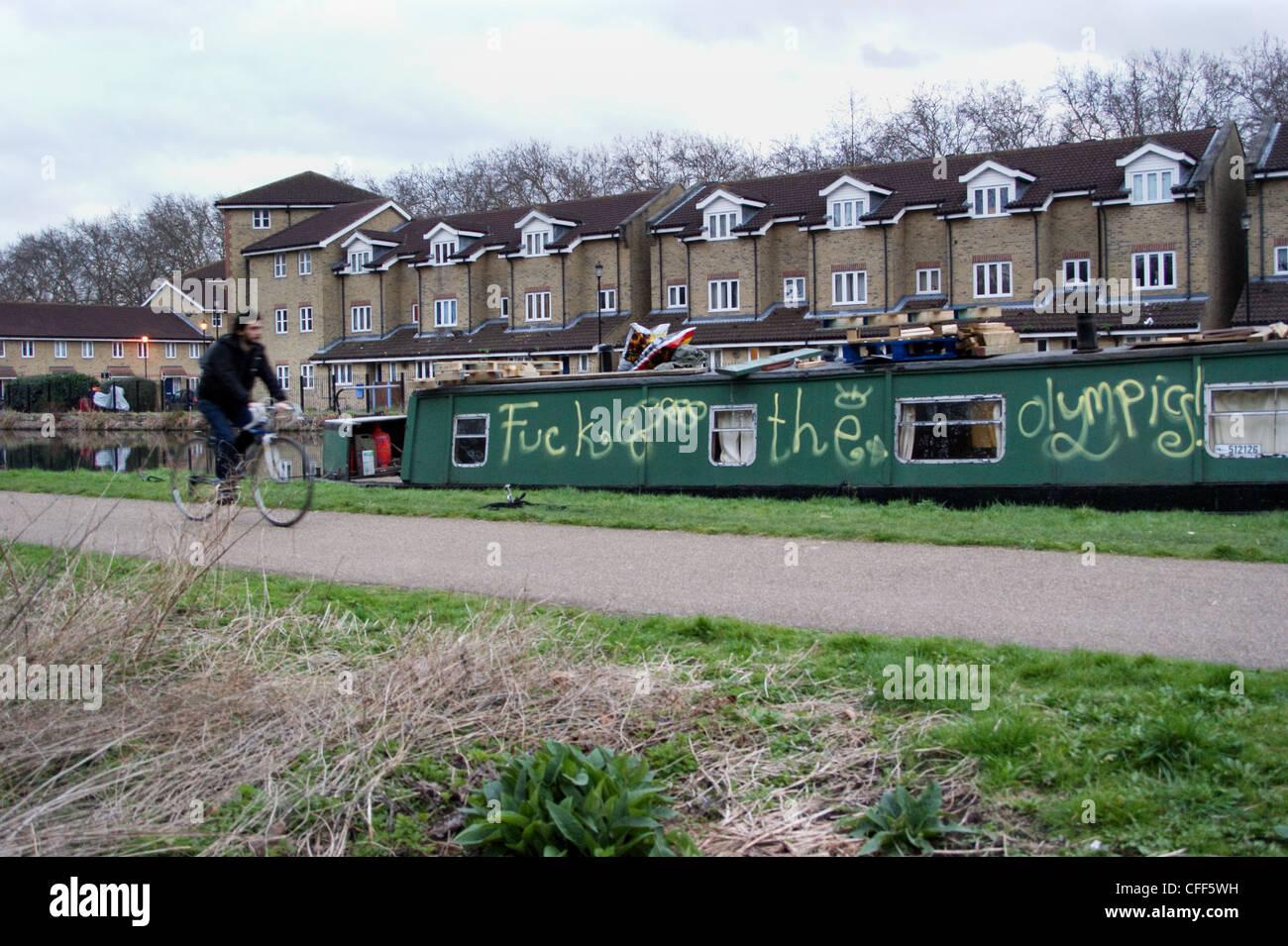 a-cyclist-passes-graffiti-on-narrowboat-