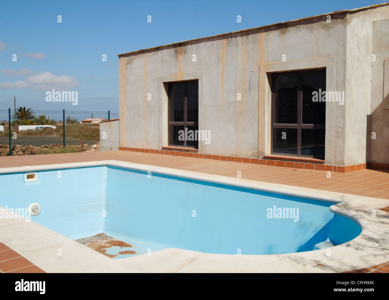 Empty swimming pool next to house at unfinished abandoned for Empty swimming pool