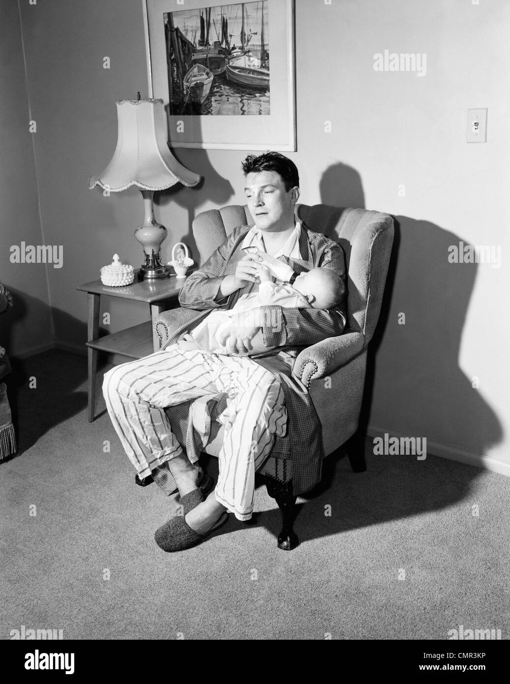 1950s Tired Father Giving Baby Bottle At Nighttime Feeding