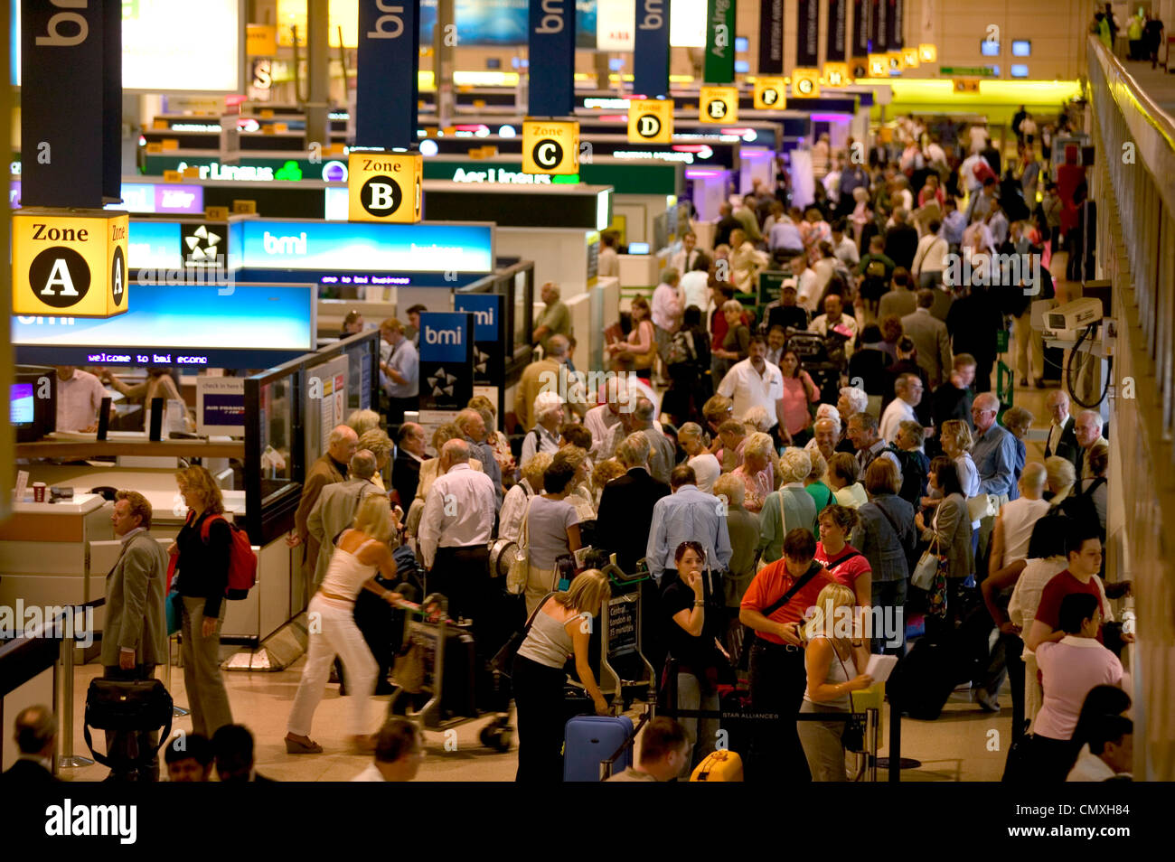 Check-in counters in busy departure lounge at Heathrow airport Stock Photo