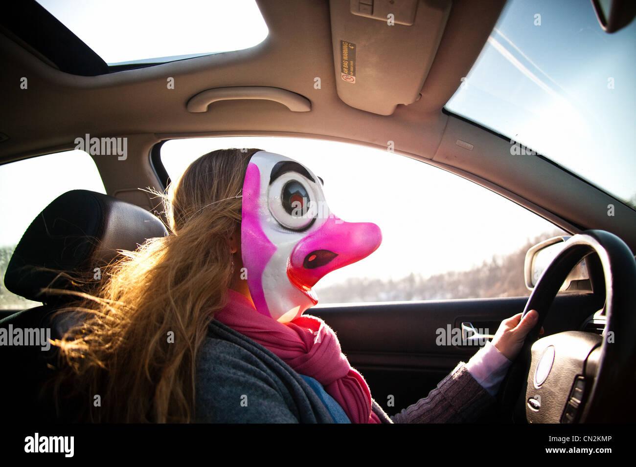 Woman driving car wearing clown mask Stock Foto