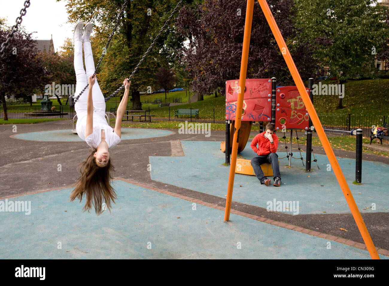 Teenage girl on swing in playground, upside down Stock Foto