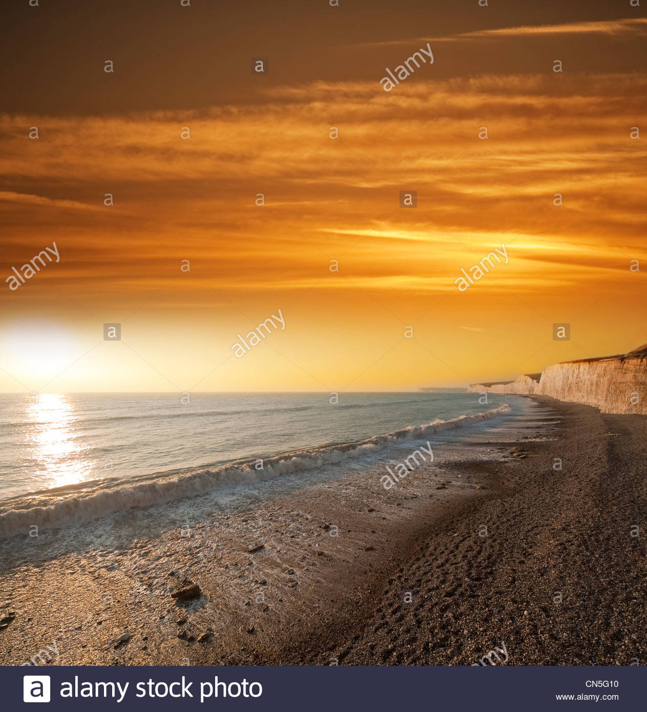 chalk-sea-cliffs-and-setting-sun-with-big-waves-on-a-shingle-beach-CN5G10.jpg
