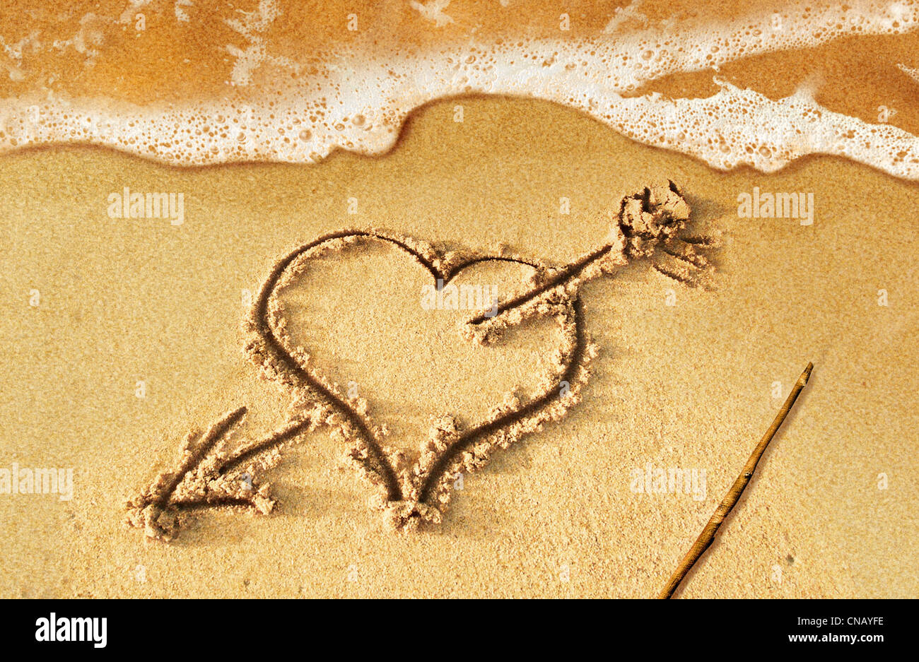Heart with arrow, as love sign, drawn on the beach shore, with some water and foam coming from the sea. Stock Foto