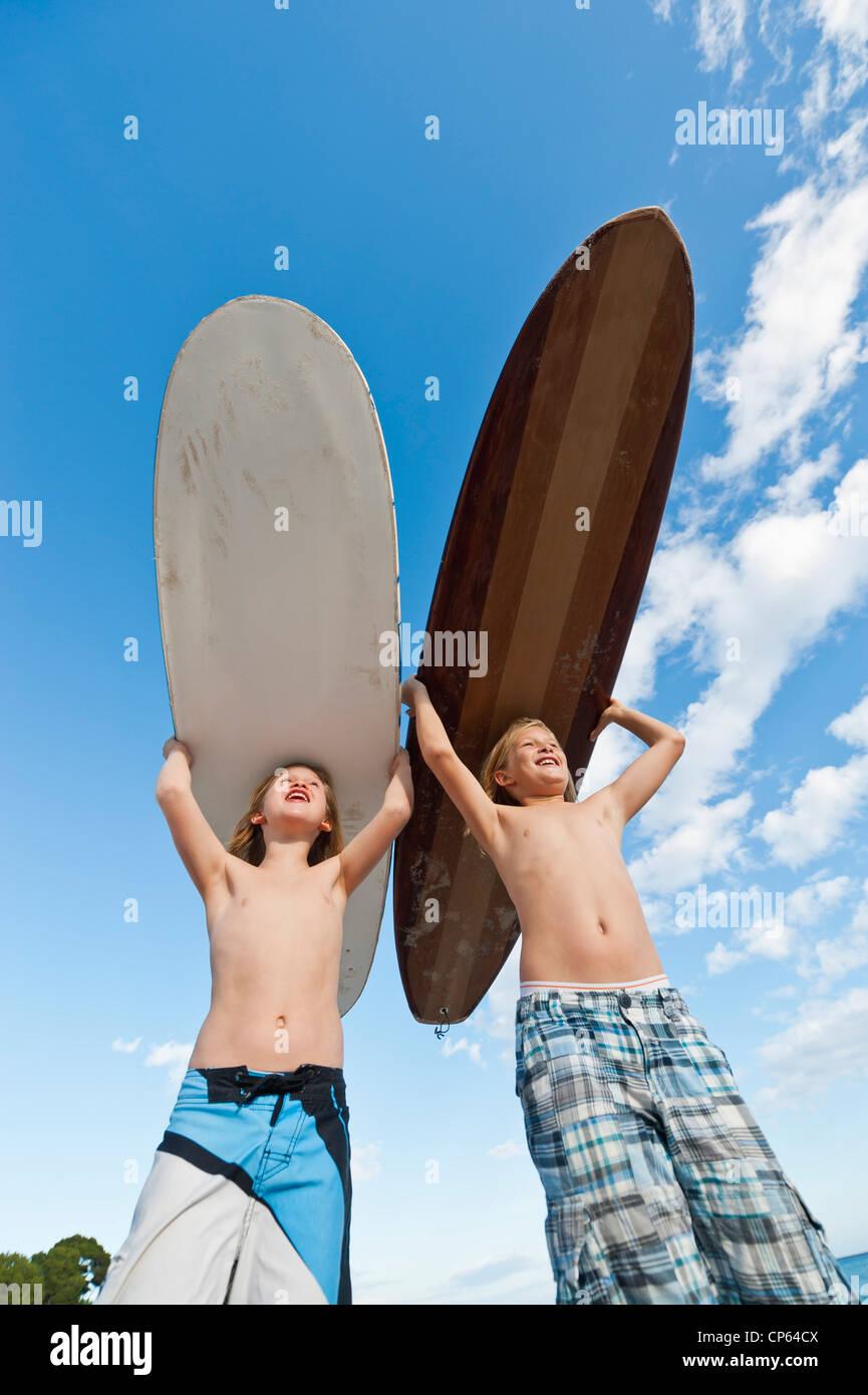 Spain, Mallorca, Children with surfboard on beach Stock Foto