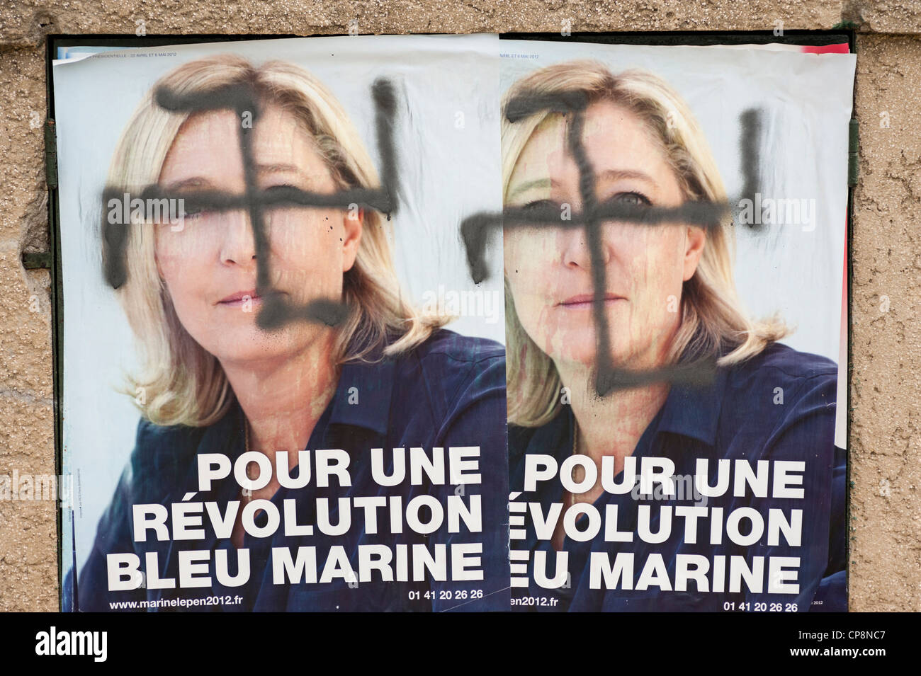 Swastika painted over posters of Marine Le Pen, France's far-right National Front political party leader - French Stock Photo
