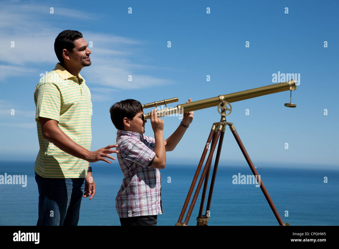 Father and son looking through a telescope Stock Photo ...