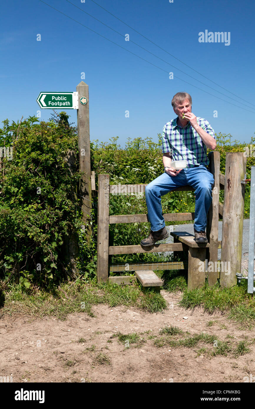 man-sitting-on-a-stile-eating-his-lunch-near-musbury-devon-CPMKBG.jpg