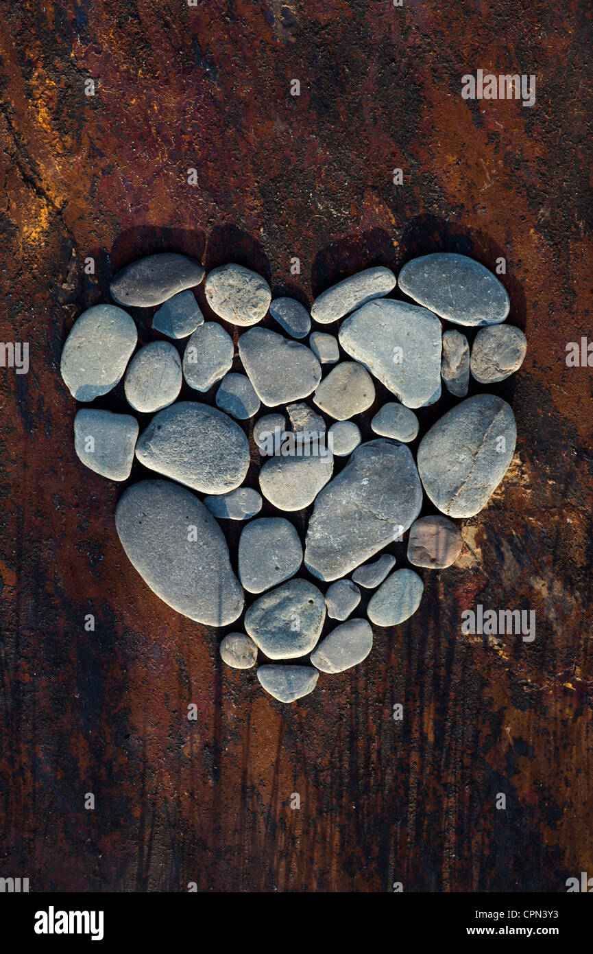 Heart shape pebbles on a texture slate background Stock Foto