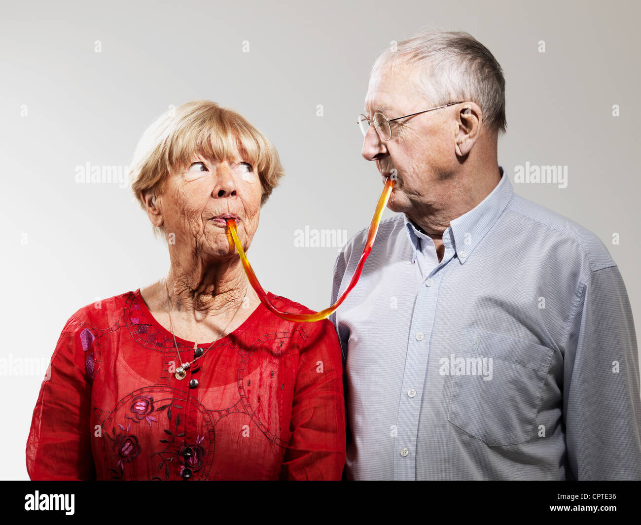 Senior couple sharing confectionery against white background Stock Foto